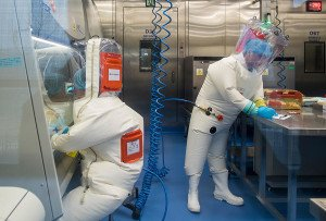 Workers are seen next to a cage with mice (R) inside the P4 laboratory in Wuhan, capital of China's Hubei province, on February 23, 2017. - The P4 epidemiological laboratory was built in co-operation with French bio-industrial firm Institut Merieux and the Chinese Academy of Sciences. (Photo by Johannes EISELE / AFP)